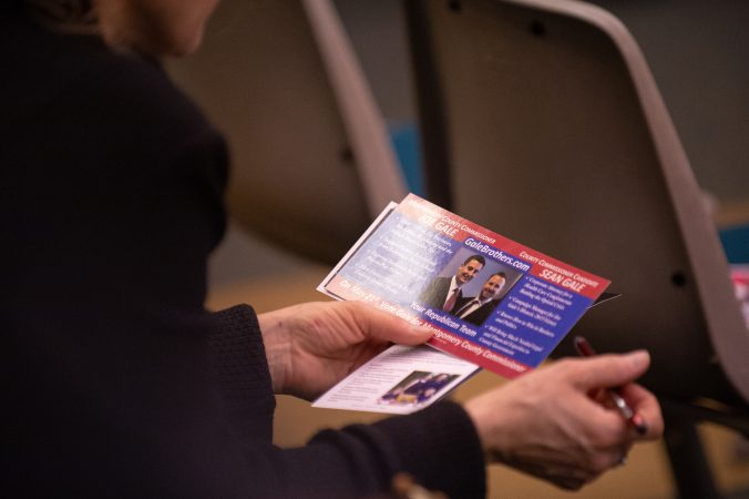 An attendee reviews materials put out by local government candidates during a forum hosted by the Montgomery County Republican Committee held at the Upper Merion Township Building in King of Prussia, Pa. on Thursday, February 28, 2019. (Kriston Jae Bethel for WHYY)