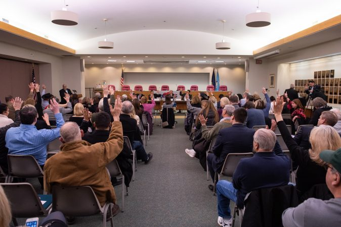 Attendees raise their hand in support of a list of traditionally conservative values prior to the start of a debate between Republican candidates for Montgomery County commissioner held at the Upper Merion Township Building in King of Prussia, Pa. on Thursday, February 28, 2019. (Kriston Jae Bethel for WHYY)