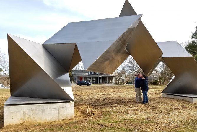 Woodmere Museum Director William Valerio (right) hugs museum Board President James Alexandre under the newly relocated sculpture,