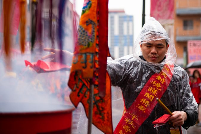 Zhang Wen tosses lit firecrackers into a barrel as part of the Hoyu Folk Culture Festival parade in Philadelphia's Chinatown on Sunday, March 31, 2019. (Kriston Jae Bethel for WHYY)