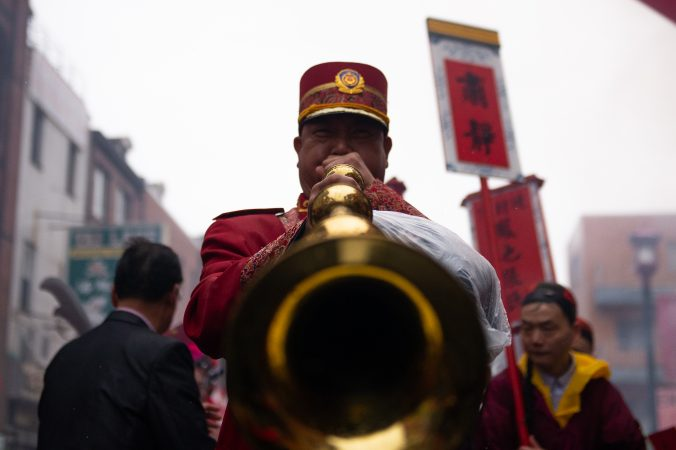 A man plays horn while participating in the Hoyu Folk Culture Festival parade in Chinatown on Sunday, March 31, 2019. (Kriston Jae Bethel for WHYY)