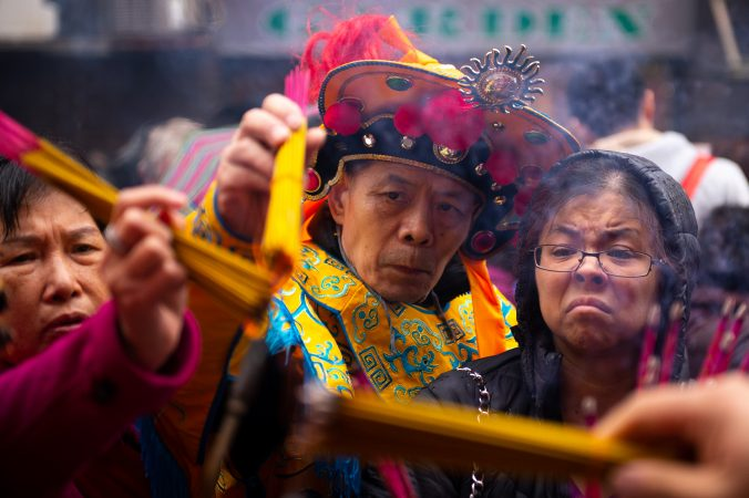 Festival-goers light incense that they will use as an offering to honor their ancestors at the Hoyu Folk Culture Festival in Chinatown on Sunday, March 31, 2019. (Kriston Jae Bethel for WHYY)