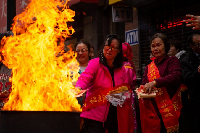 Festival-goers toss paper money into flames as a way to honor their ancestors during the Hoyu Folk Culture Festival in Chinatown on Sunday, March 31, 2019. (Kriston Jae Bethel for WHYY)