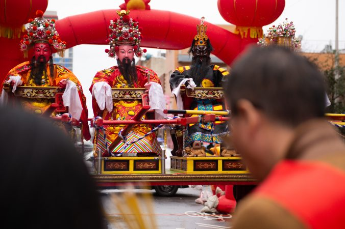 An effigy of General Humin is flanked by two others, as festival goers offer incense during the Hoyu Folk Culture Festival in Chinatown on Sunday, March 31, 2019. The festival celebrates the more than 1,000th birthday of General Humin, said to have been a scholar and a fighter, who helped build the city of Fuzhou. (Kriston Jae Bethel for WHYY)