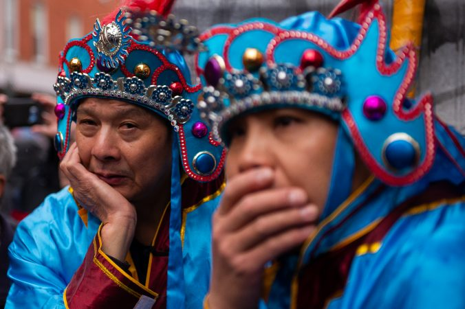 Wearing costumes of their own, two men watch a traditional Chinese opera performance during the Hoyu Folk Culture Festival in Chinatown on Sunday, March 31, 2019. (Kriston Jae Bethel for WHYY)