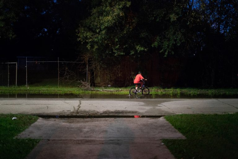 A boy rides his bike through still water after a thunderstorm in the Lakewood area of East Houston, which flooded during Hurricane Harvey. (Claire Harbage/NPR)