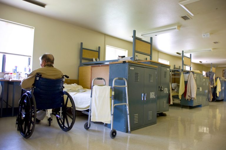 In this photo taken Tuesday, Aug. 3, 2010, an inmate sits in is his wheelchair near his bed (Sandy Summers Russell/AP Photo)