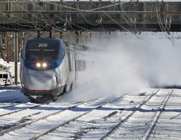 In this file photo, an Amtrak Acela train blows snow as it passes through the Princeton Junction station in West Windsor, N.J. (Mel Evans/AP Photo)