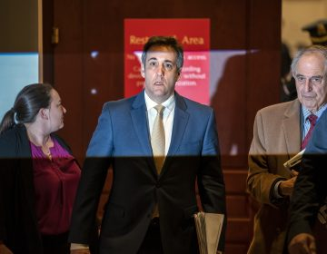 Michael Cohen, President Donald Trump's former lawyer, is illuminated by a camera flash as he leaves a closed-door interview with his attorney Lanny Davis, (right), after testifying before the House Intelligence Committee, on Capitol Hill in Washington, Thursday, Feb. 28, 2019. (J. Scott Applewhite/AP Photo)