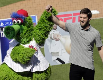 Bryce Harper stands with the Philadelphia Phillies mascot Phanatic before being introduced as a Phillies player during a news conference at the team's spring training baseball facility, Saturday, March 2, 2019, in Clearwater, Fla. Harper and the Phillies agreed to a $330 million, 13-year contract, the largest deal in baseball history. (Lynne Sladky/AP Photo)