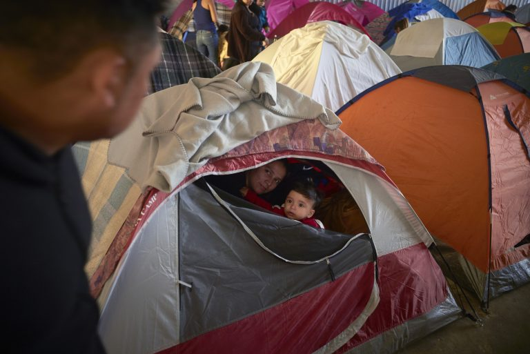 In this March 5, 2019, image, Ruth Aracely Monroy, (center), looks out of the family's tent alongside her 10-month-old son, Joshua, as her husband, Juan Carlos Perla, (left), passes inside a shelter for migrants in Tijuana, Mexico. (Gregory Bull/AP Photo)