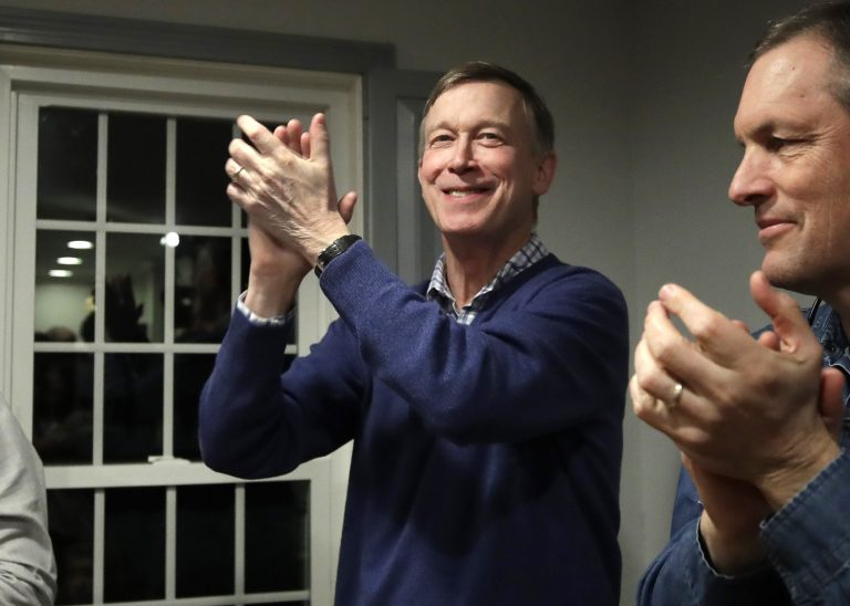 FILE - In this Feb. 13, 2019, file photo, former Colorado Gov. John Hickenlooper, left, applauds at a campaign house party in Manchester, N.H. While the Democratic primary field has shifted left, polls show registered Democratic voters just want someone who can beat Donald Trump. That's led to a potential contradiction being worked over by primary voters. Is the best route to victory to build a liberal movement to win converts or choose a more moderate candidate who can appeal to swing voters? (Elise Amendola/AP Photo, File)