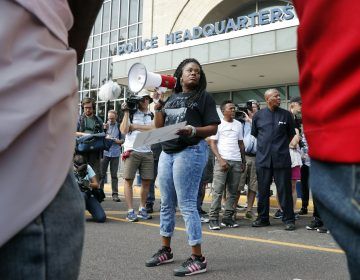 In this Sept. 17, 2017 file photo, Cori Bush speaks on a bullhorn to protesters outside the St. Louis Police Department headquarters in St. Louis. Six deaths, all involving men with connections to protests in Ferguson, Missouri, drew attention on social media and speculation in the activist community that something sinister was at play. Bush said her car has been run off the road, her home has been vandalized, and in 2014 someone shot a bullet into her car, narrowly missing her daughter, who was 13 at the time. Activists and observers remain puzzled, especially since people involved in the protests continue to face harassment and threats. (Jeff Roberson/AP Photo)