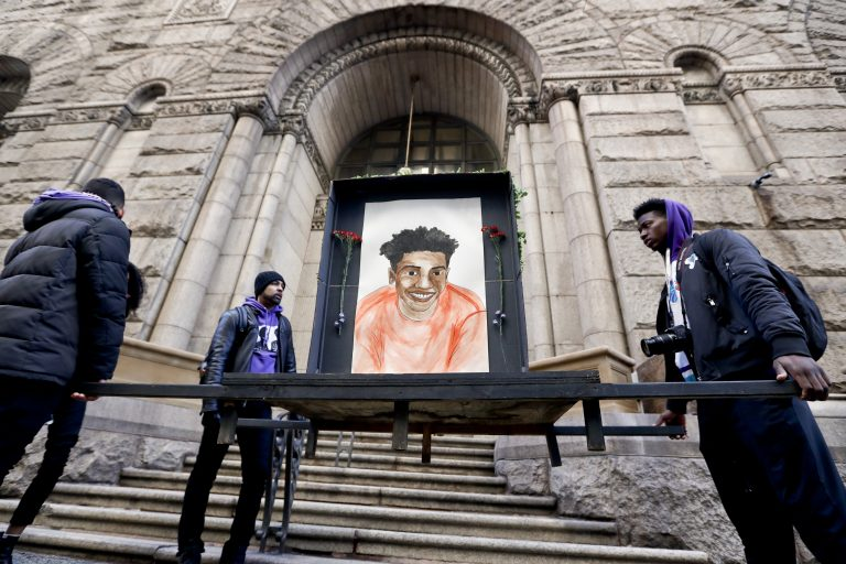 Farooq Al-Said, left, Jasiri X, center, and Jarrion Manning, right, hold a memorial display with a drawing of Antwon Rose II in front of the court house on the first day of the trial for Michael Rosfeld, a former police officer in East Pittsburgh, Pa., begins on Tuesday, March 19, 2019, in Pittsburgh. (Keith Srakocic/AP Photo)