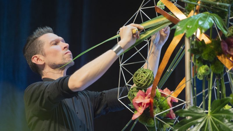 Australia's Bart Hassam puts the finishing touches on his arrangement, which took first place in the final round of the FTD Interflora World Cup. (Jonathan Wilson for WHYY)