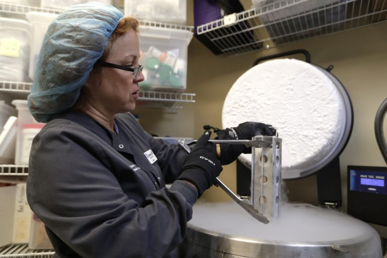 Medical tech removes a container with frozen embryos and sperm being stored in liquid nitrogen at a fertility clinic. (Lynne Sladky/ AP Photo)