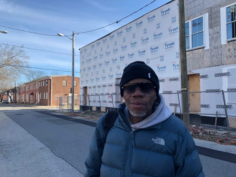 """Troy Curtis calls it a """"waste of money"""" that homes being built and slated for renovation on Wilmington's East Side have languished without progress for months. (Cris Barrish/WHYY)"""