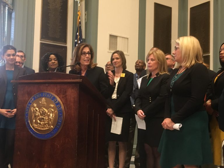 Delaware Attorney General Kathy Jennings unveils a package of criminal justice reform bills surrounded by state lawmakers in Legislative Hall in Dover. (Mark Eichmann/WHYY)