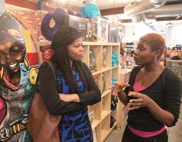 Erin Wilson, left, state director for U.S. Sen. Bob Casey, talks with Ariell Johnson, owner of Amalgam Comics and Coffeehouse. (Abdul Sulayman/Tribune Chief Photographer)