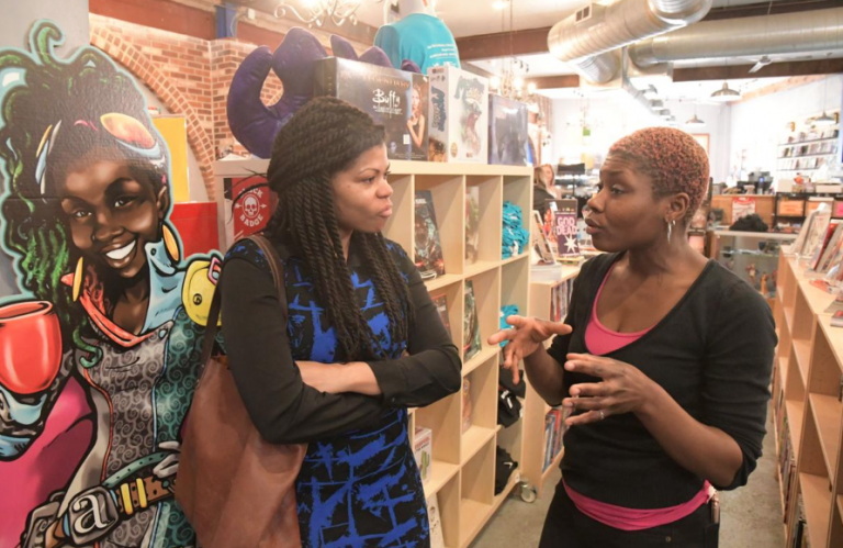 Erin Wilson, left, state director for U.S. Sen. Bob Casey, talks with Ariell Johnson, owner of Amalgam Comics and Coffeehouse. (Abdul Sulayman/Tribune Chief Photographer)