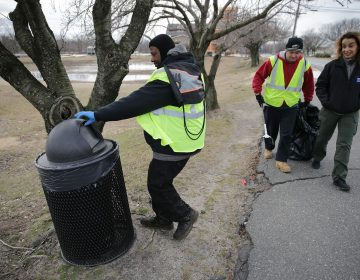 Malcolm Flowers (left) checks a trash can as Cristina