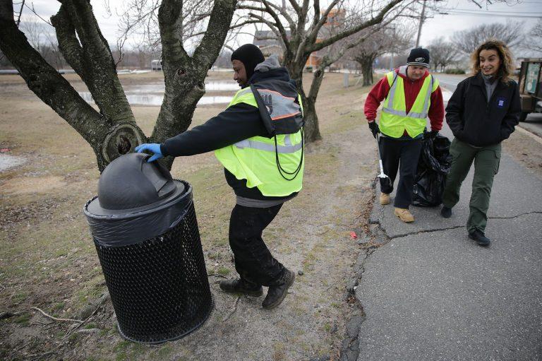 Malcolm Flowers (left) checks a trash can as Cristina