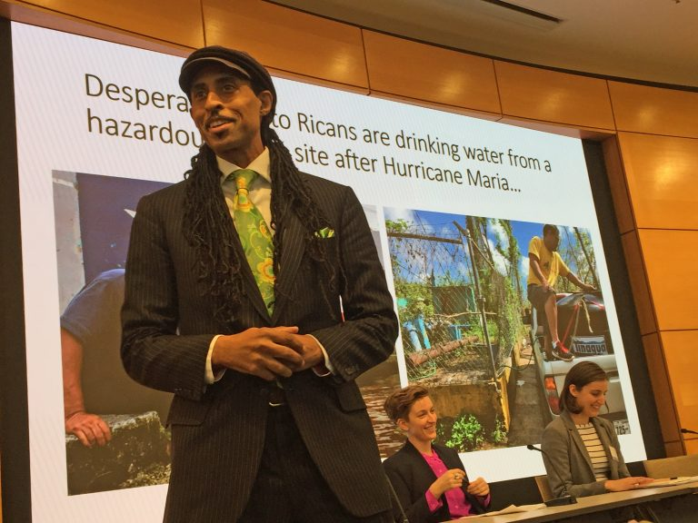 Mustafa Santiago Ali (left) discusses water system vulnerabilities in the U.S. with Zoe Roller (middle) and Emily Kutil (right) at the 12th Annual Global Water Alliance Conference. (Dana Bate/WHYY)