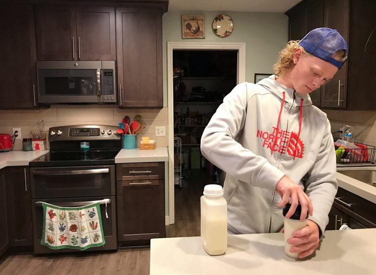 Jonah Reeder prepares a special protein shake that helps him manage a metabolic condition called phenylketonuria. (Julia Ritchey/KUER)