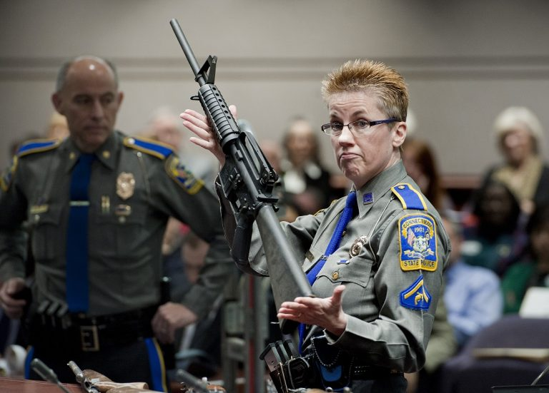 Detective Barbara J. Mattson, of the Connecticut State Police, holds up a Bushmaster AR-15 rifle, the same make and model of gun used by Adam Lanza in the Sandy Hook School shooting. (AP Photo/Jessica Hill, File)