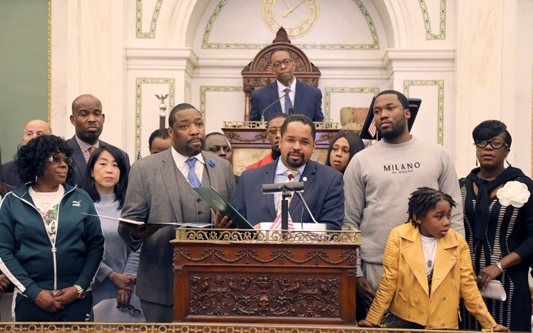 Meek Mill (right) and his son listen as Pennsylvania state Sen. Sharif Street (center) presents a state resolution in his honor. (Tom MacDonald/WHYY)