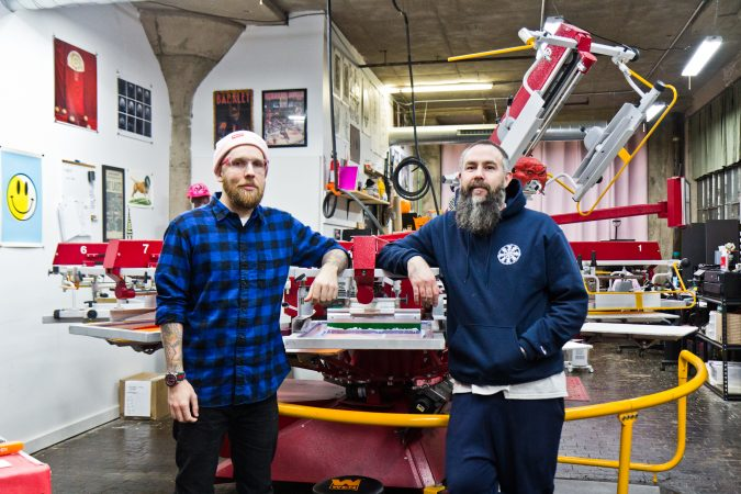Dylan Houser (left) and Mason Warner are two of the owners ofPink's Inks, located in the Globe Dye Works building. (Kimberly Paynter/WHYY)