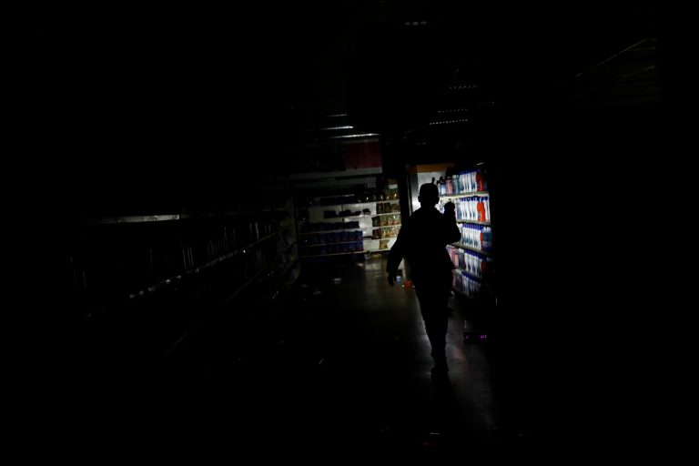 A worker inspects damage in a supermarket in Caracas on Sunday after it was looted during a days-long blackout in Venezuela. (Carlos Garcia Rawlins/Reuters)