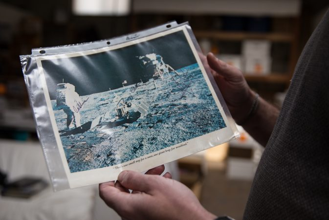 J.J. Tiziou holds a print of the moon landing signed by Buzz Aldrin, Neil Armstrong and Michael Collins.  The photograph is part of his late father, French journalist Jacques Tiziou's, collection of memorabilia from the Apollo missions and space program. (Lindsay Lazarski/WHYY)