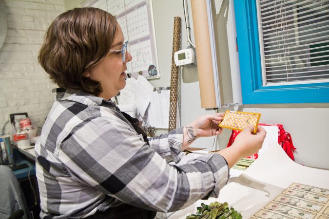 Jewelry maker and sculpture artist Stacey Lee Webber shows an embroidery work in progress. (Kimberly Paynter/WHYY)