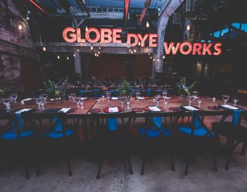 The original Globe Dye Works sign now takes center stage in the former boiler room. (Courtesy of Birchtree Catering/BeauMonde Originals)
