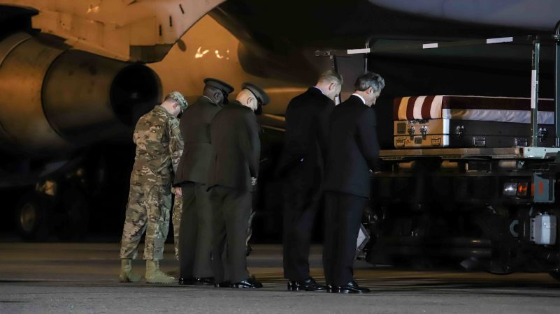 Delaware Governor John Carney prays in front of the transfer case of Staff Sgt. Christopher K.A. Slutman, 43, of Newark, Delaware, during a dignified transfer at Dover Air Force Base Thursday, Apr. 11, 2019,  in Dover, Del. (Saquan Stimpson for WHYY)Sgt. Slutman died April 8 while conducting combat operations in Parwan province, Afghanistan.