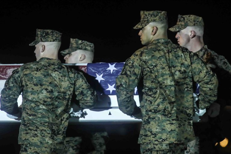A U.S. Marine Corps carry team transfers the remains of Staff Sgt. Christopher K.A. Slutman, 43, of Newark, Delaware, during a dignified transfer at Dover Air Force Base Thursday, Apr. 11, 2019,  in Dover, DE. Sgt. Slutman died April 8 while conducting combat operations in Parwan province, Afghanistan. (Saquan Stimpson for WHYY)