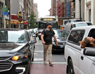 A pedestrian threads his way through traffic at the intersection of Broad and Chestnut streets. (Emma Lee/WHYY)