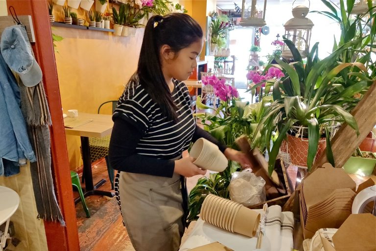 An employee at the Coco Thai Bistro lays out some of the shop's new biodegradable products.  (Xavier Lopez for WHYY)