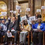Candidates hold yes signs aloft signaling their agreement with the proposal of a representative speaker. Twenty candidates for city council attended a candidates forum at Congregation Rodeph Shalom on March 24, 2019. (Jonathan Wilson for WHYY)