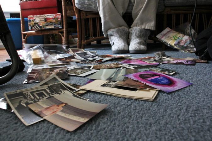 Childhood photos collect at her feet as Patricia Cahill talks about the sexual abuse she says started when she was 15 years old. (Emma Lee/WHYY)