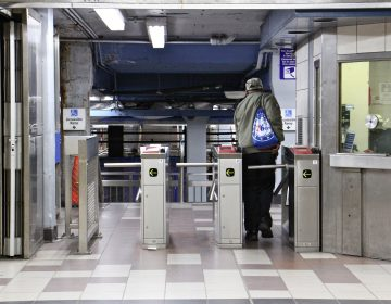 A SEPTA rider passes through the turnstile at the 8th and Market station. (Emma Lee/WHYY)