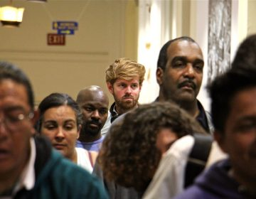 PlanPhilly reporter Ryan Briggs (center) waits in line at City Hall with other Philadelphians to get a city ID. (Emma Lee/WHYY)