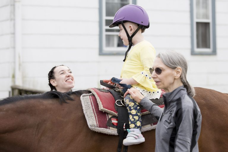 Volunteers Gabby Fink (left) and Carol Rowehl (right) help Emma Reed, 6, to stay upright on horse Prince Caspian on April 7, 2019. Reed is a participant in Pegasus Therapeutic Riding Academy's new Stepping Forward program for children of first responders. (Rachel Wisniewski for WHYY)