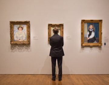 "A visitor admires impressionist portraits at ""The Impressionist's Eye"" exhibit at the Philadelphia Museum of Art. (Kimberly Paynter/WHYY)"