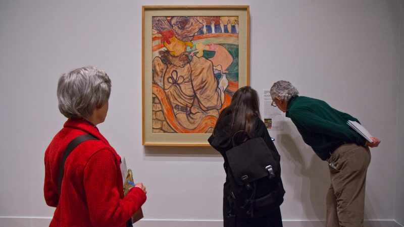 "Visitors admire Henri de Toulouse-Lautrec's ""The Dancer and the Five Stiff Shirts"" at ""The Impressionist's Eye"" exhibit at the Philadelphia Museum of Art. (Kimberly Paynter/WHYY)"