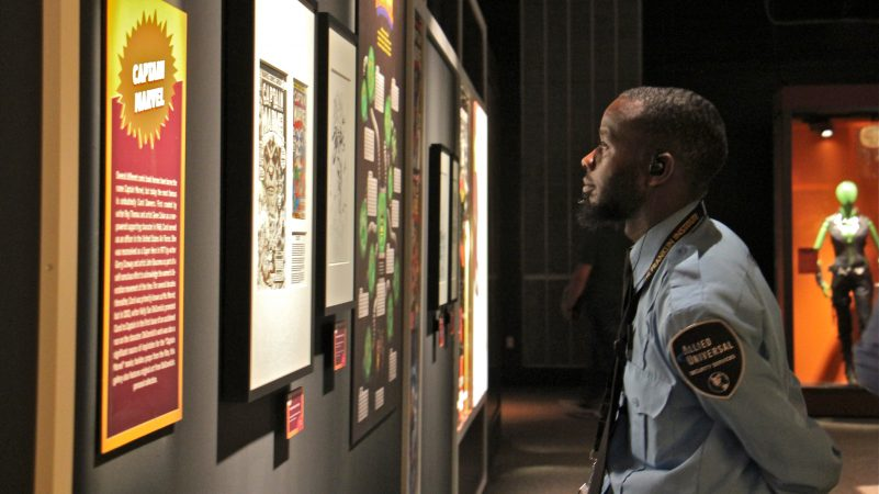 A security guard at the Franklin Institute pauses to take in some of the Marvel Comics exhibit. The more than 300 objects in the sprawling exhibit have an insured value of more than $25 million, according to curator Ben Saunders. (Emma Lee/WHYY)
