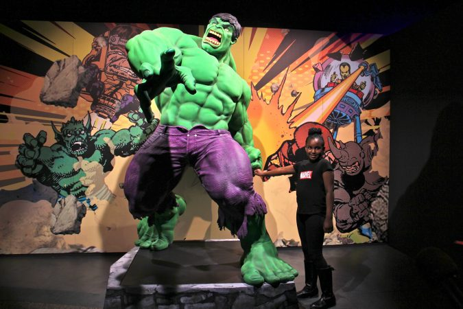Tiana Sirmans of New Castle, Delaware, poses with The Incredible Hulk during a preview of the Marvel Comics exhibit at the Franklin Institute. (Emma Lee/WHYY)