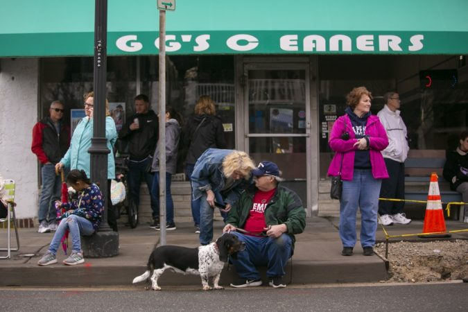 Spectators sit along Asbury Avenue as hundreds of basset hounds march down the street during BoardWaddle on Saturday, April 13, 2019, in Ocean City. (Miguel Martinez for WHYY)