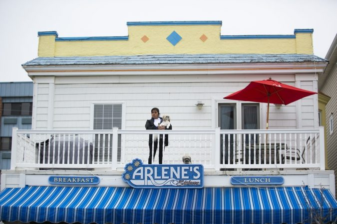 A spectator watches from a balcony on Asbury Avenue as hundreds of basset  hounds march down the street during BoardWaddle on Saturday, April 13, 2019, in Ocean City. (Miguel Martinez for WHYY)